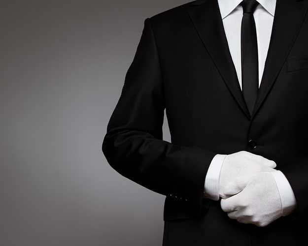 Person wearing a suit and tie with only their neck to waste in the frame