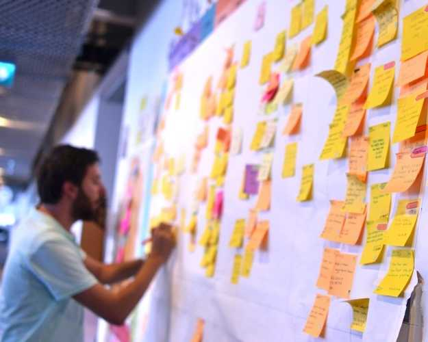 Person writes on sticky note at wall covered in sticky notes