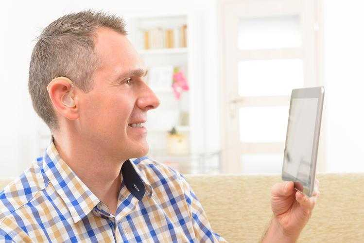 Hearing impaired person holding up and looking at a tablet