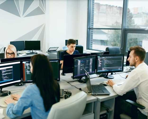 Group of 4 office workers sit at their desks which are grouped together in a rectangular setup