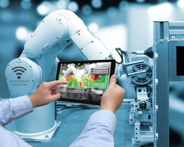 Close up of person's arms and hands holding out a tablet which they are using to control a robotic arm in the background, from inside of a laboratory