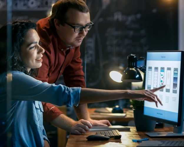 One person pointing to a computer screen and showing their work to another person who stands next to them looking