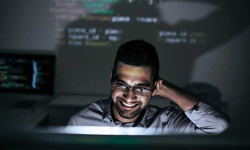 Person smiling as the light from their computer screen illuminates their face in the dark room and computer code is projected onto the wall behind them