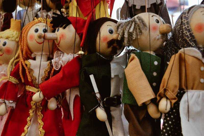 Group of marionette puppets hang from strings