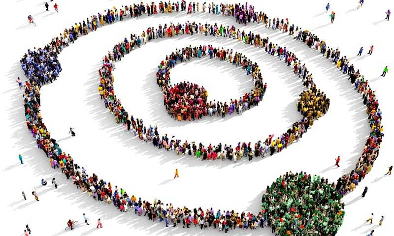 Cartoon image of hundreds of people forming rings on a plain white background while some of the people form clusters of people within the ring that are all wearing similar color clothing