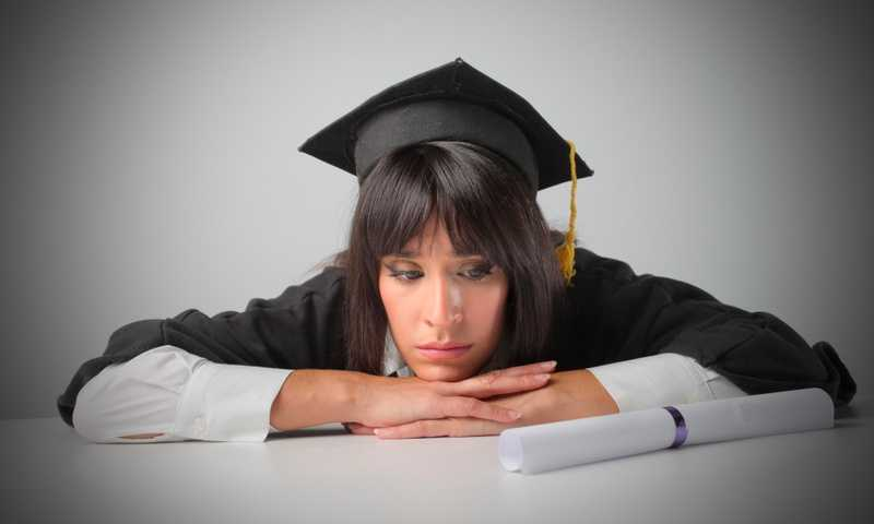 Person wearing cap and gown sits at table resting their chin on their crossed hands while staring at a rolled up college degree sitting on the table with a look of sadness