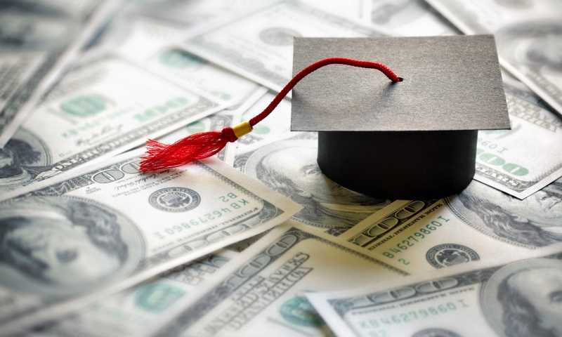Graduation cap sits on pile of 100 dollar bills