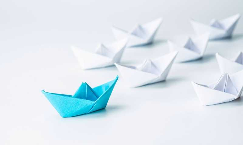 A blue folded paper boat with several white folded paper boats behind it