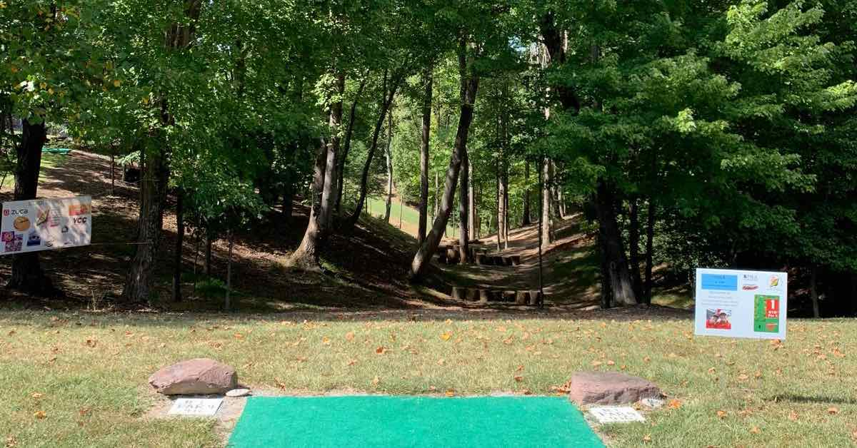 A very well-maintained turf tee pad in front of a wooded fairway that is a dip between two hills