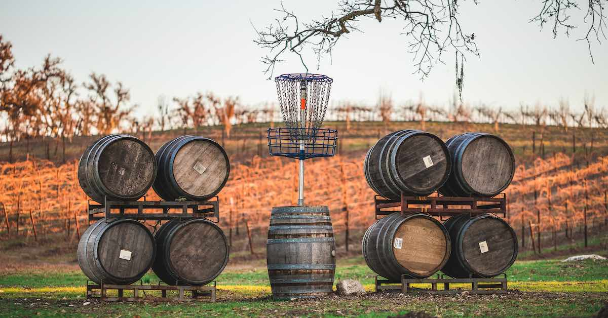 A disc golf basket stands on top of a wine barrel surrounded by other barrels with vineyards in the background