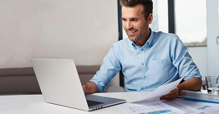 Foto de um homem sentado à frente do seu notebook, vestindo camisa azul clara. Ele segura papéis e está um pouco sorridente. É um homem branco, um pouco barbado com idade aproximada de 30 anos.