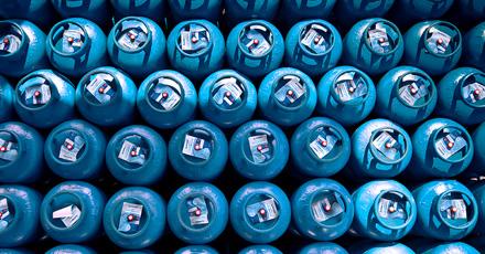 Foto vista de cima de vários botijões azuis enfileirados com selos de seguraça.