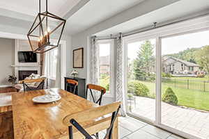 dining room with wood table and white fiberglass sliding patio door from Infinity