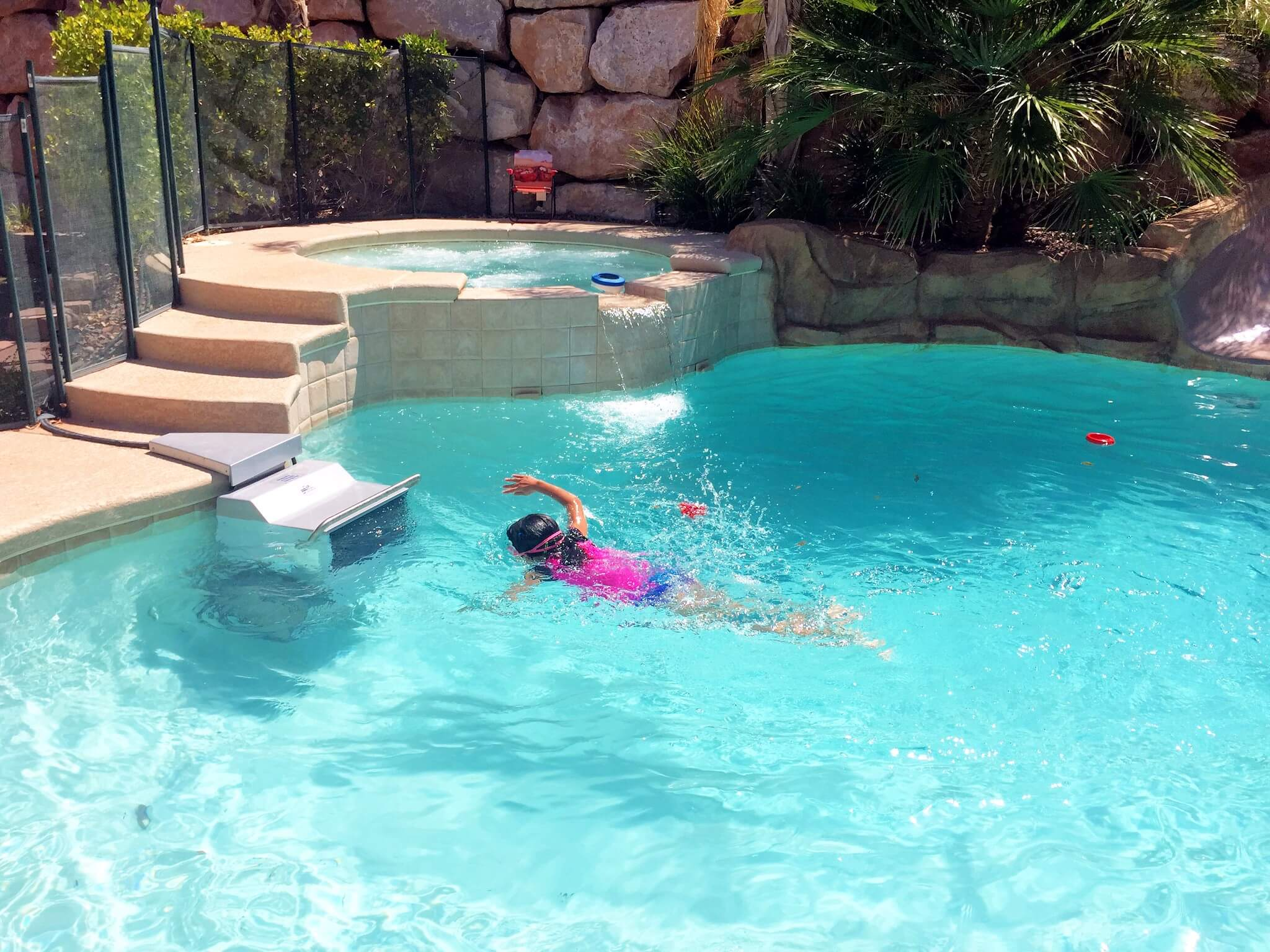 a young swimmer uses the Endless Pools Fastlane in a backyard pool