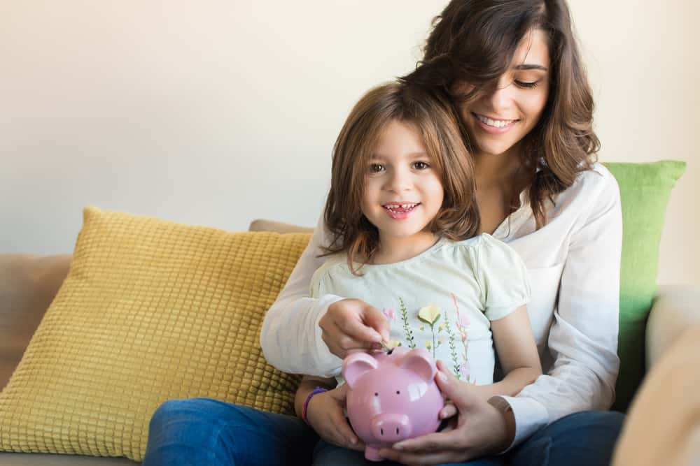 mom and daughter saving money in piggy bank