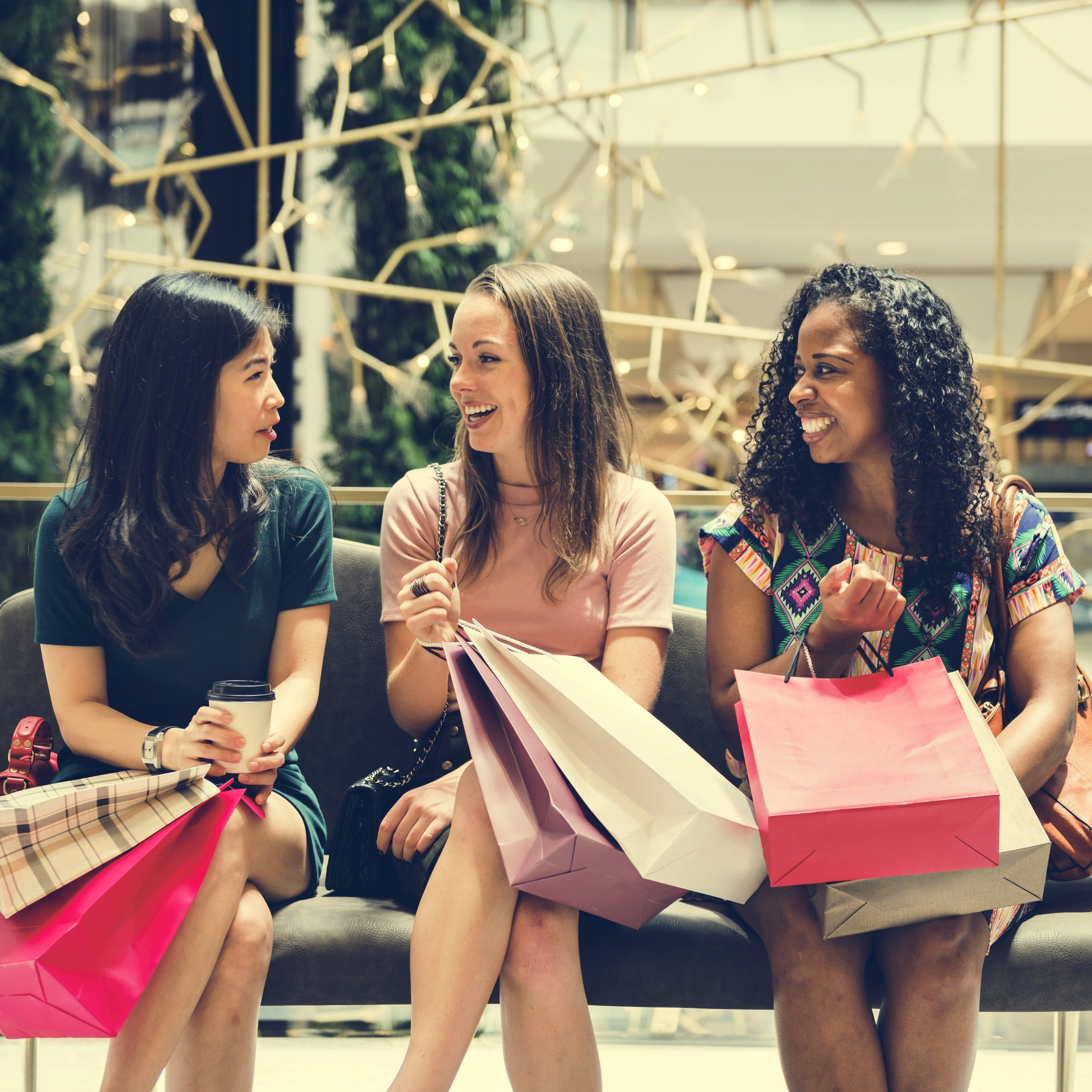 three girls sitting at the mall after shopping