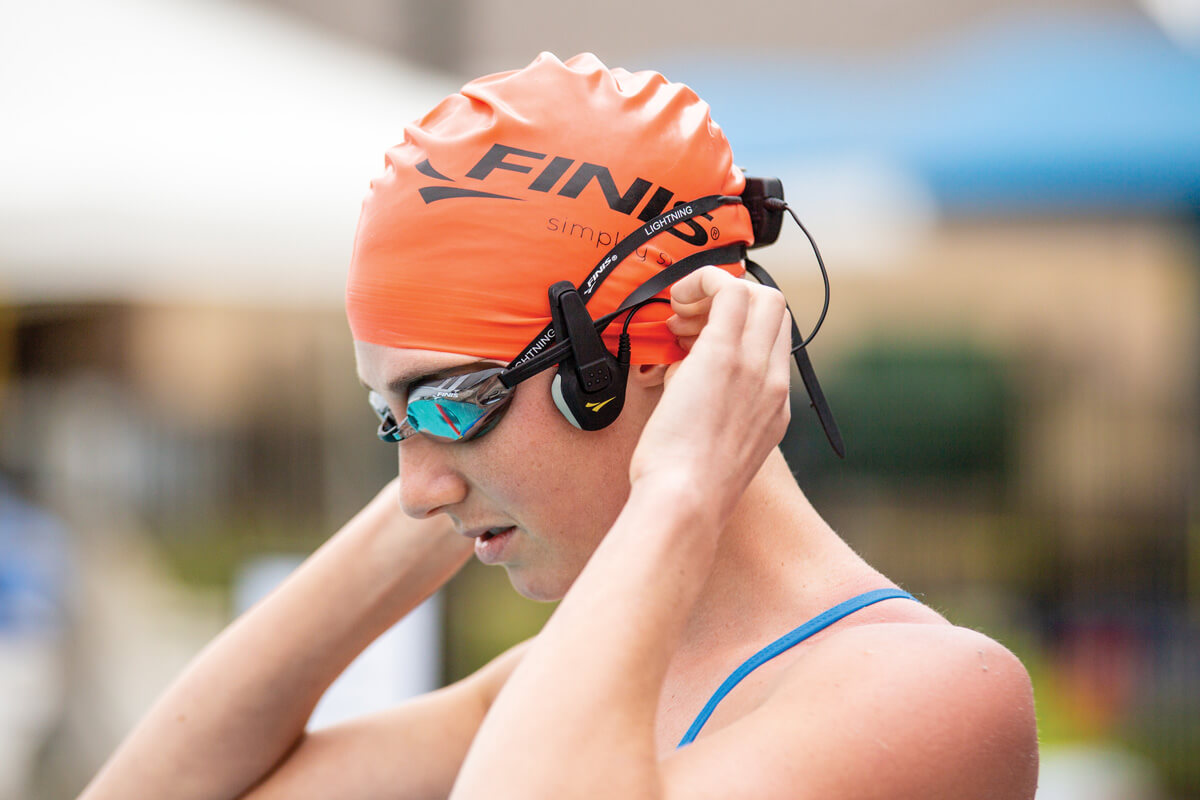 a swimmer adjusts the FINIS Swim Coach Communicator