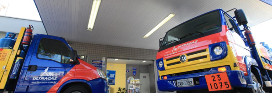 Foto de dois caminhões da Ultragaz,  nas cores azul, vermelho e amarelo estacionado embaixo do andaime de uma revenda da marca.