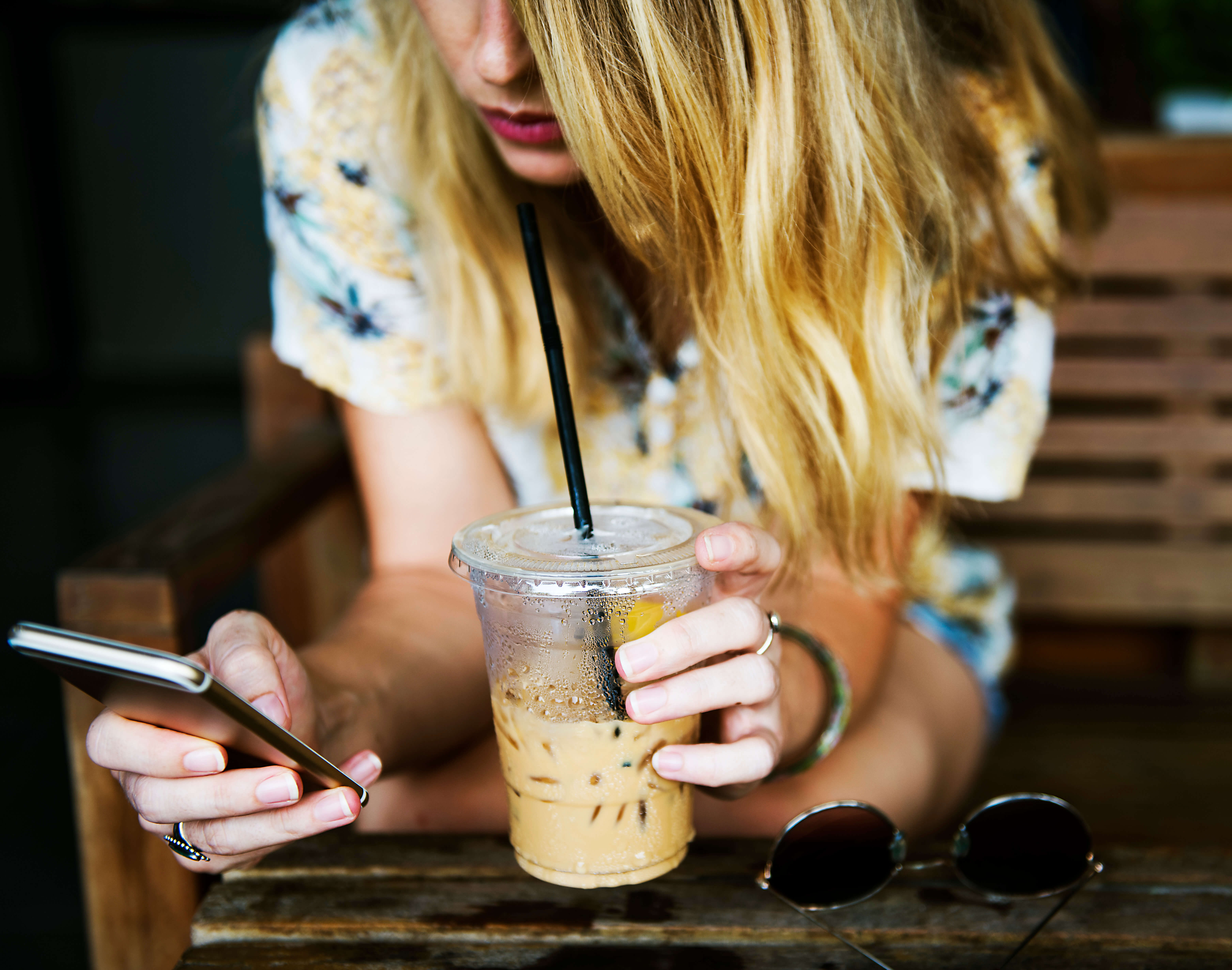 woman-holding-iced-coffee-and-phone