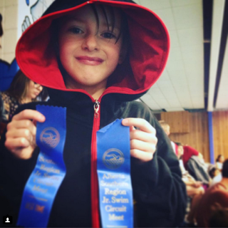 A boy diagnosed with ADHD holds his swimming ribbons