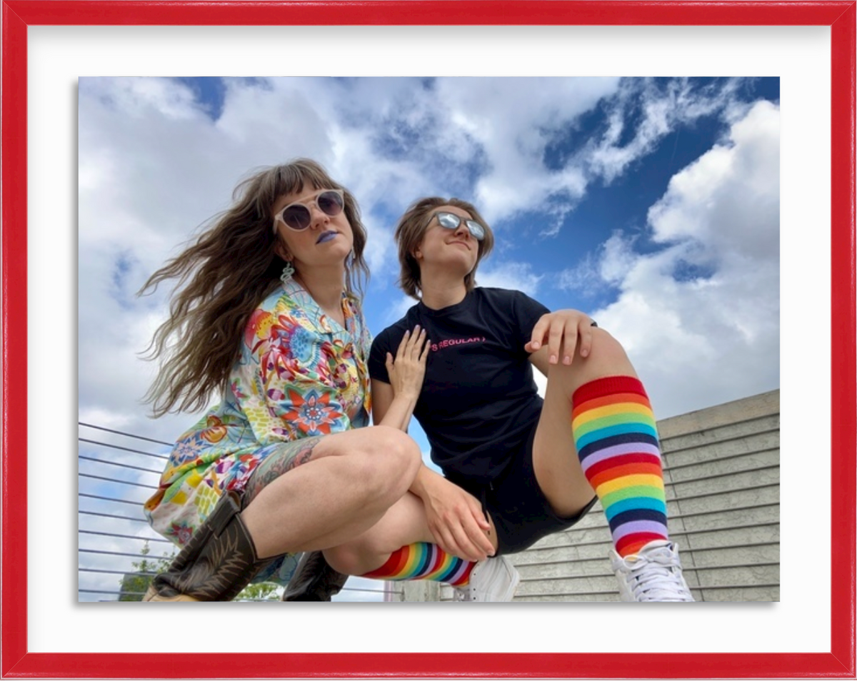 Photo of two women on rooftop celebrating gay pride in red Madrid frame