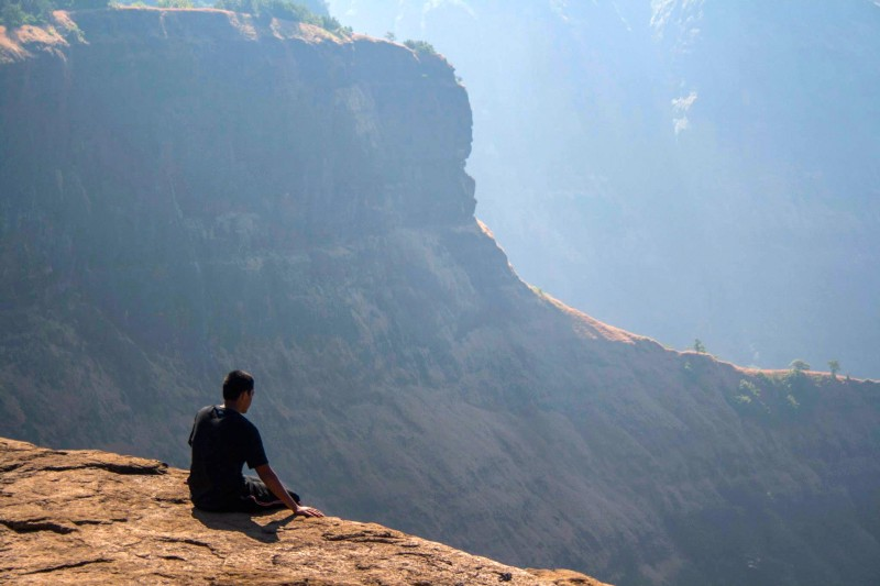 man sitting off cliff thinking of mistakes