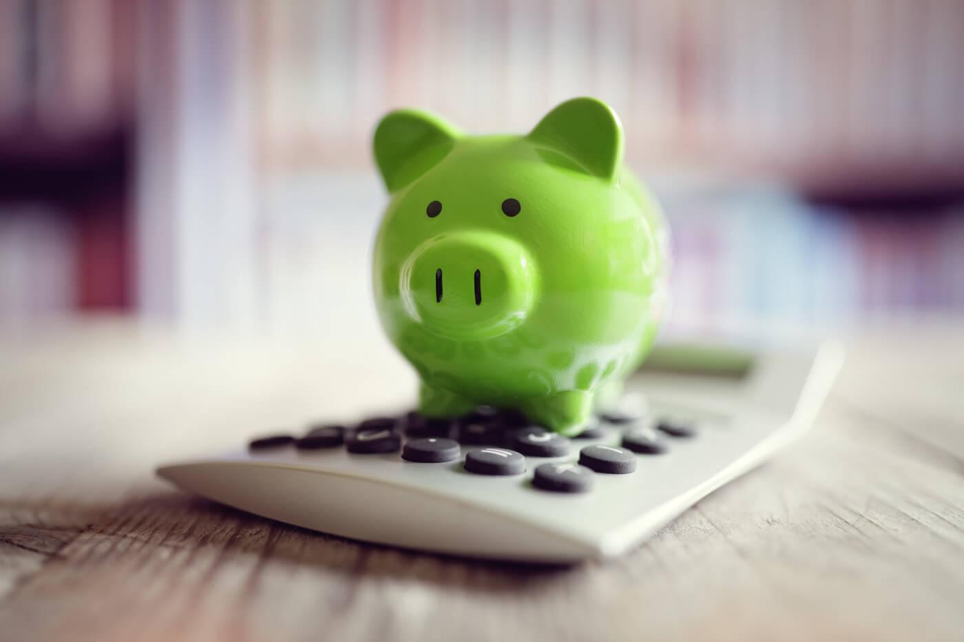 green piggy bank on a calculator