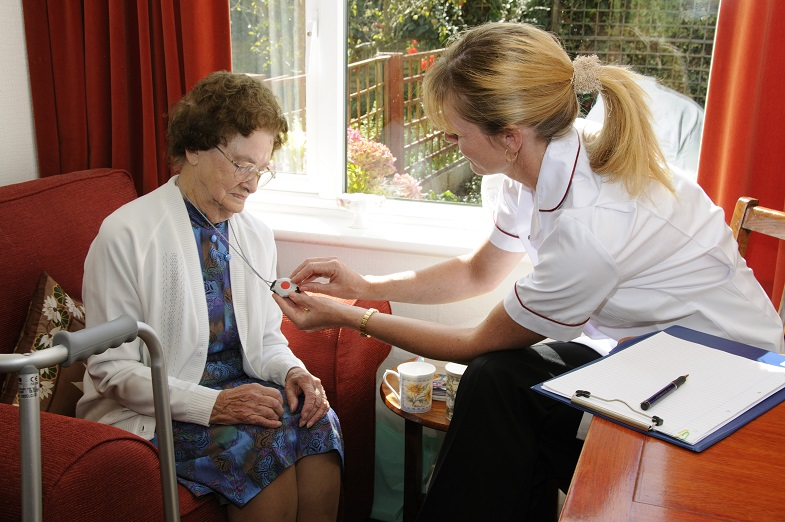 elderly woman receiving a fall detection medical alert system with GPS distress rescue button on lanyard