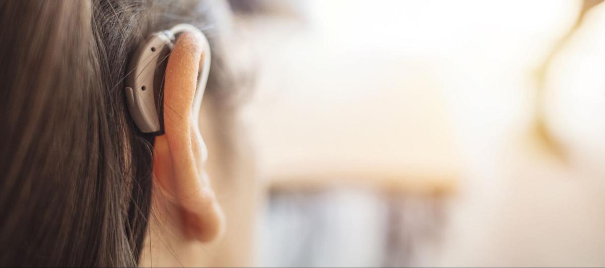 Amplifon: Close up shot of a woman's ear wearing a hearing aid