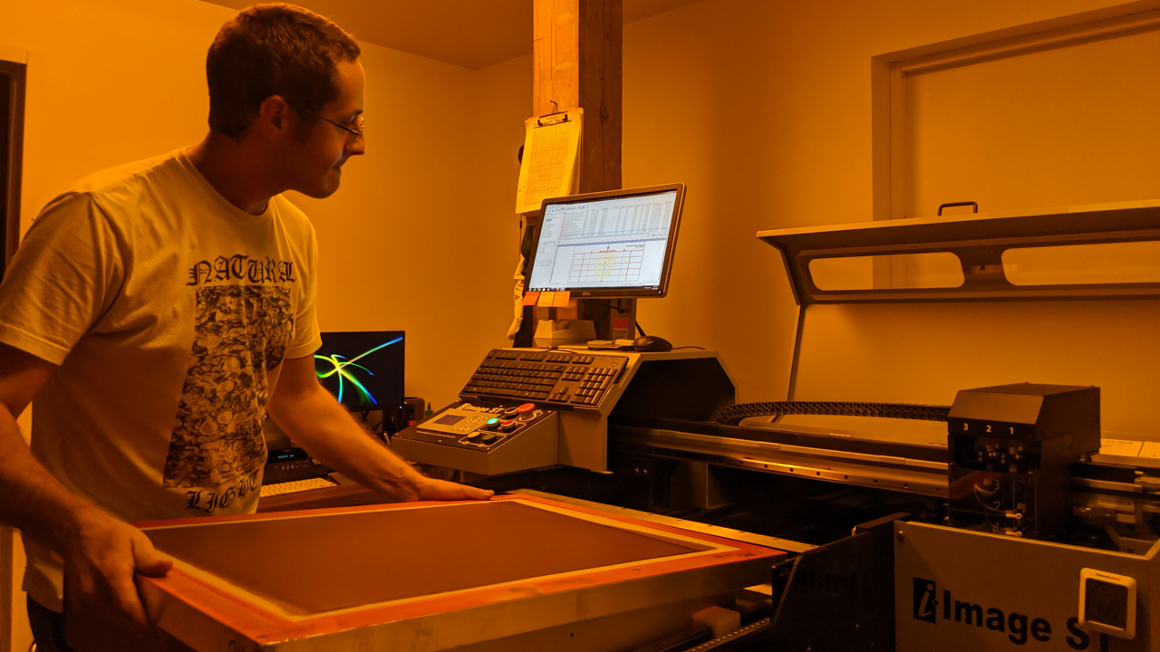 A computer-to-screen system (M&R i-Image) with a screen technician loading a screen printing screen.