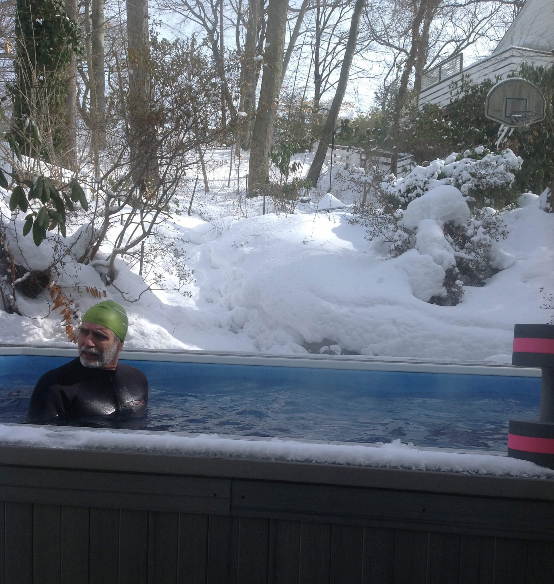 A swimmer in a wetsuit in the Endless Pools swimming machine after snowfall.