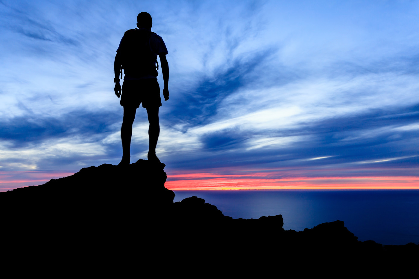 man standing on a mountain watching the sunset