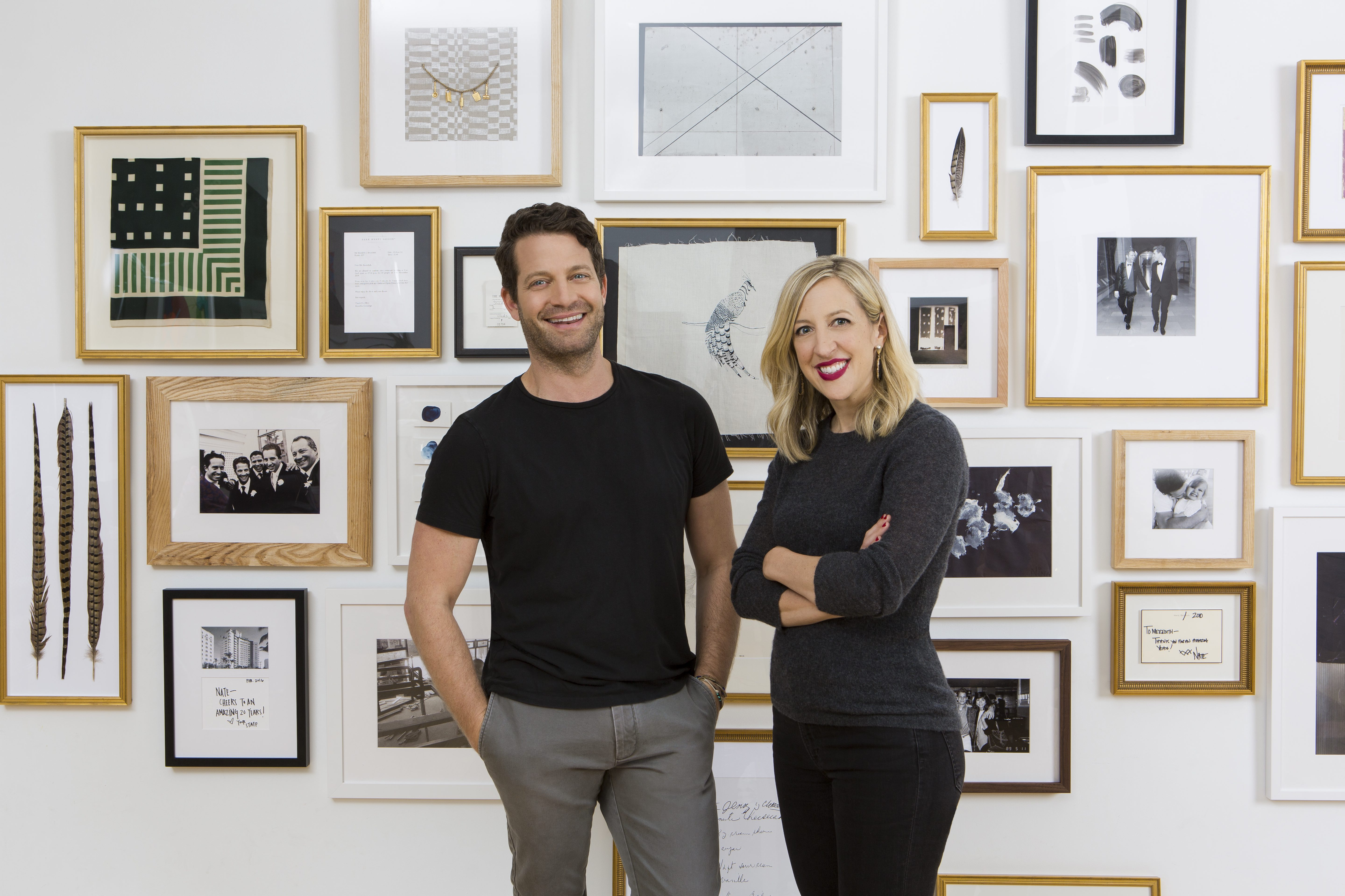 Susan Tynan and Nate Berkus in front of floor to ceiling gallery wall with gold frames