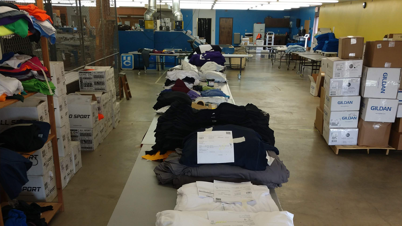 Setting up shirts and garments for screen printing at a print shop.