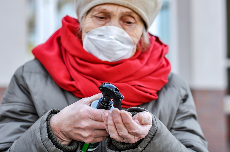 elderly woman wearing surgical mask to prevent coronavirus - germiciding hands for COVID-19
