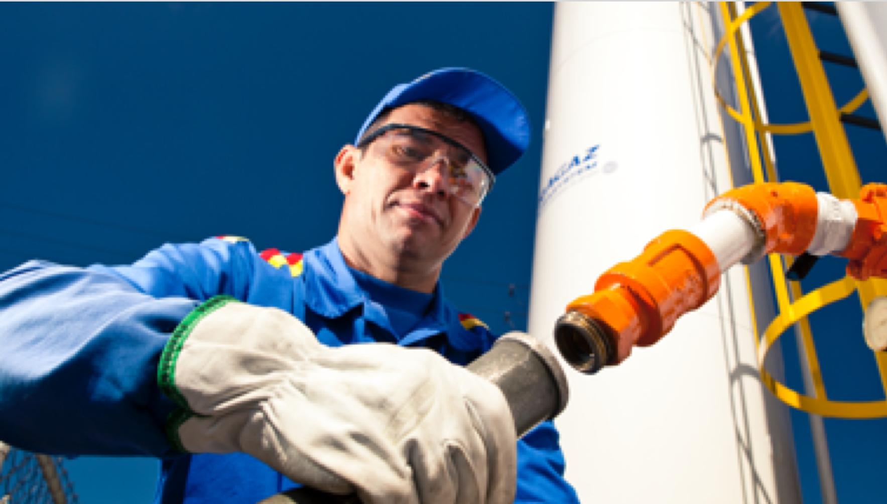 Foto do funcionário Ultragaz vestido com um macacão azul segurando um tubo de metal cinza. Ao fundo temos um cilindro muito grande,  branco com símbolo ultragaz estampado.  Ele está inclinado como se estivesse preste a conectar o tubo em outro tubo na cor laranja.