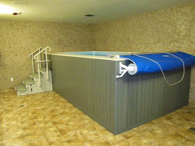 an Endless Pools swimming machine installed above-ground in a basement