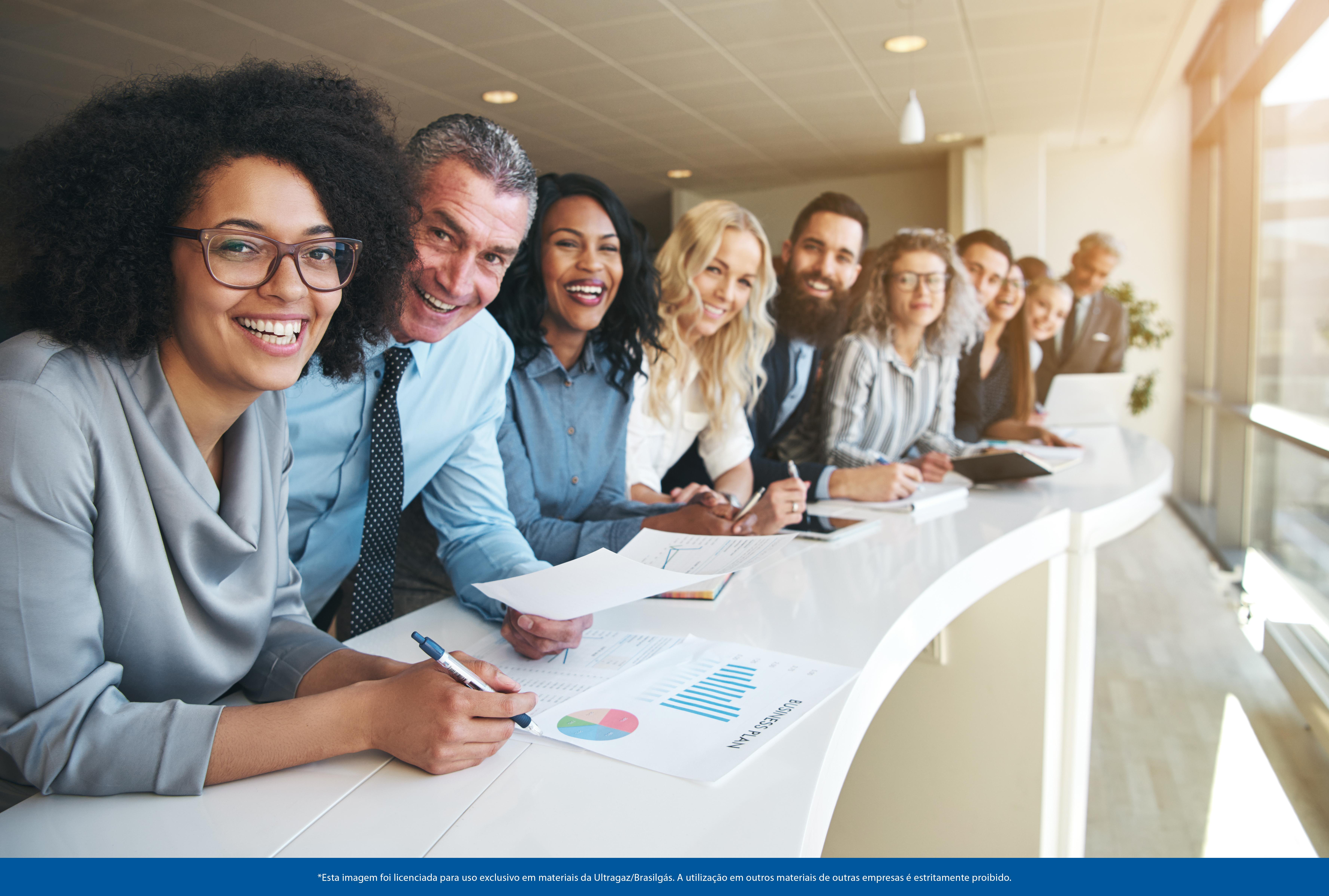 Foto de 10 pessoas sentadas em um balcão, todos de etnias muito diferentes e sorrindo bastante, com papéis nas mãos.