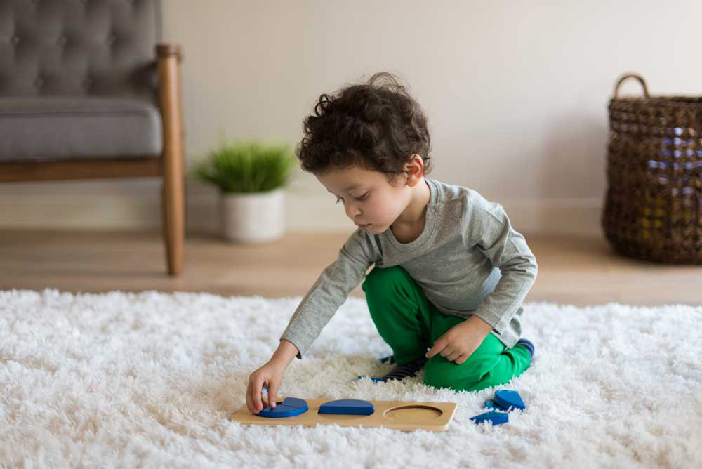 toddler wearing gray and green solving a wooden puzzle