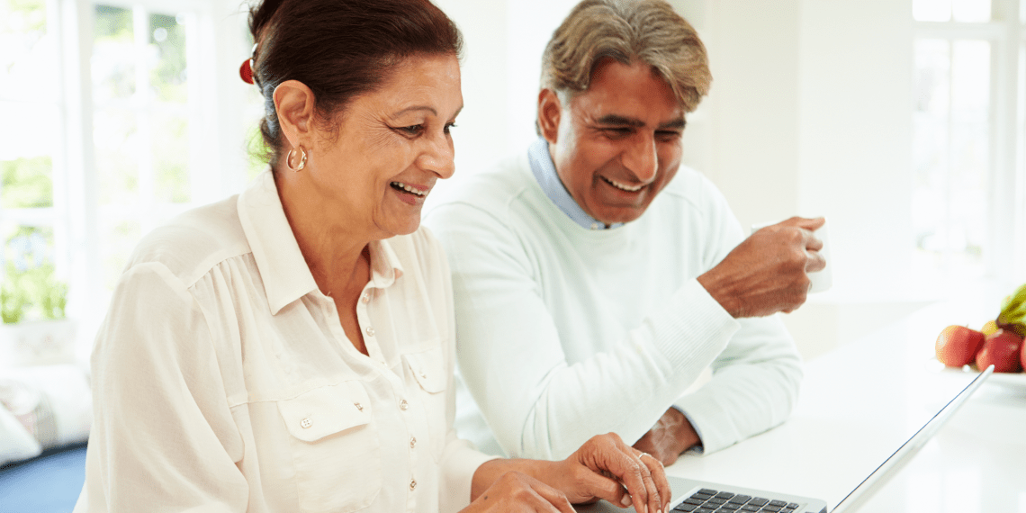 couple smiling and looking at laptop