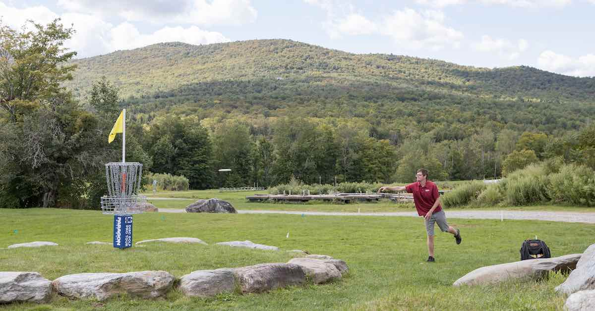 A disc golfer putts at a basket with a backdrop of green mountains