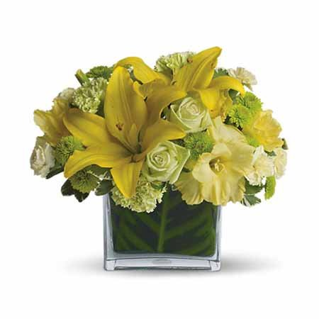 Yellow lily pale green roses inside a leaf lined square vase