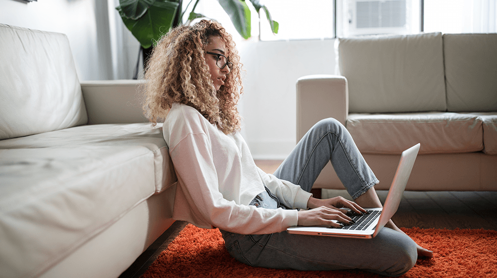 Woman sitting on floor typing on laptop