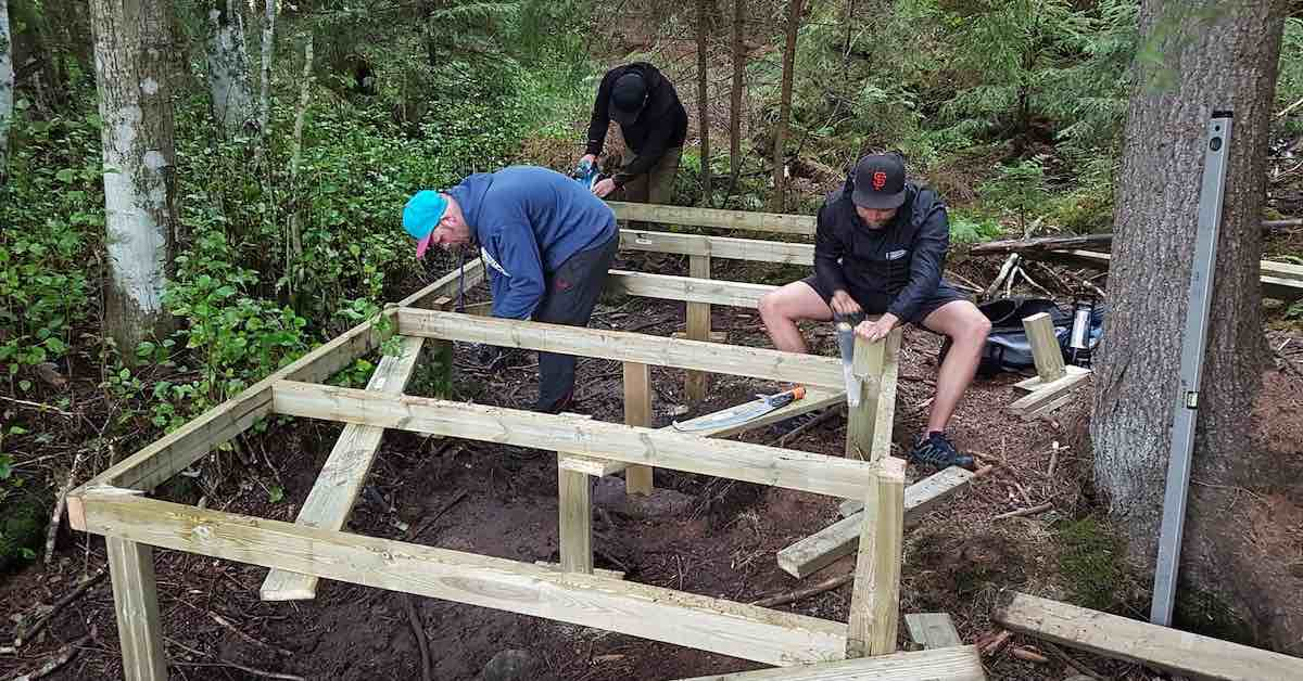 Men with saws constructing the foundations of a disc golf tee pad