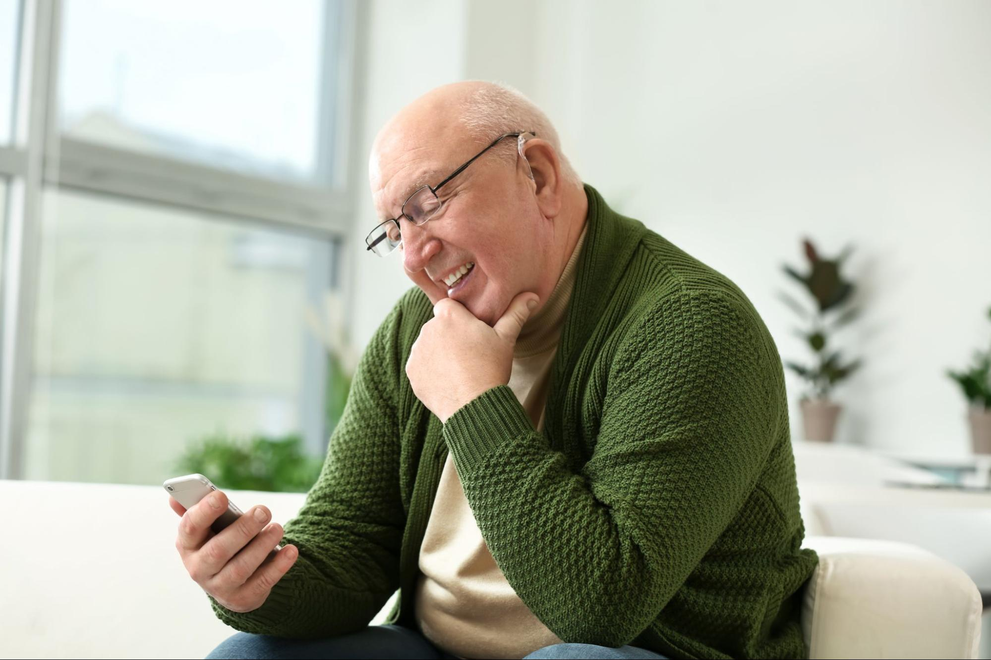 Hearing Care Solutions: old man smiling while looking at his phone