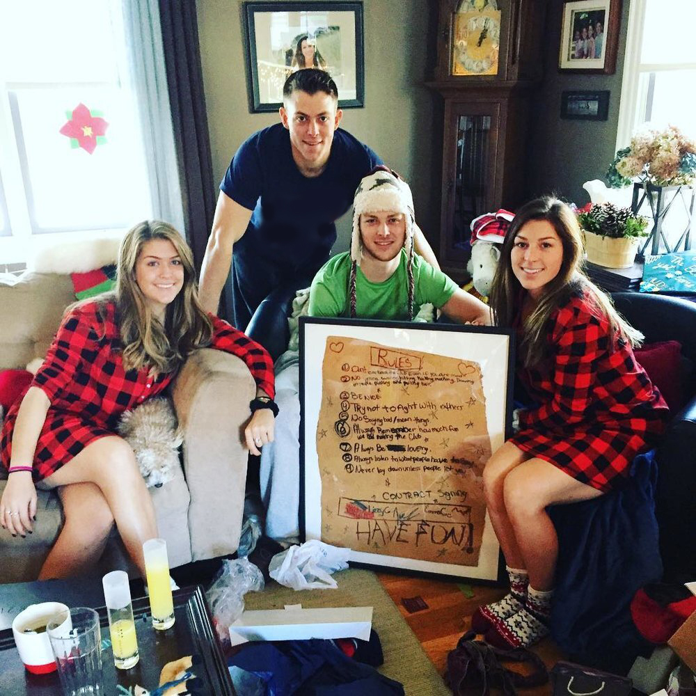family on Christmas morning with framed cardboard sign