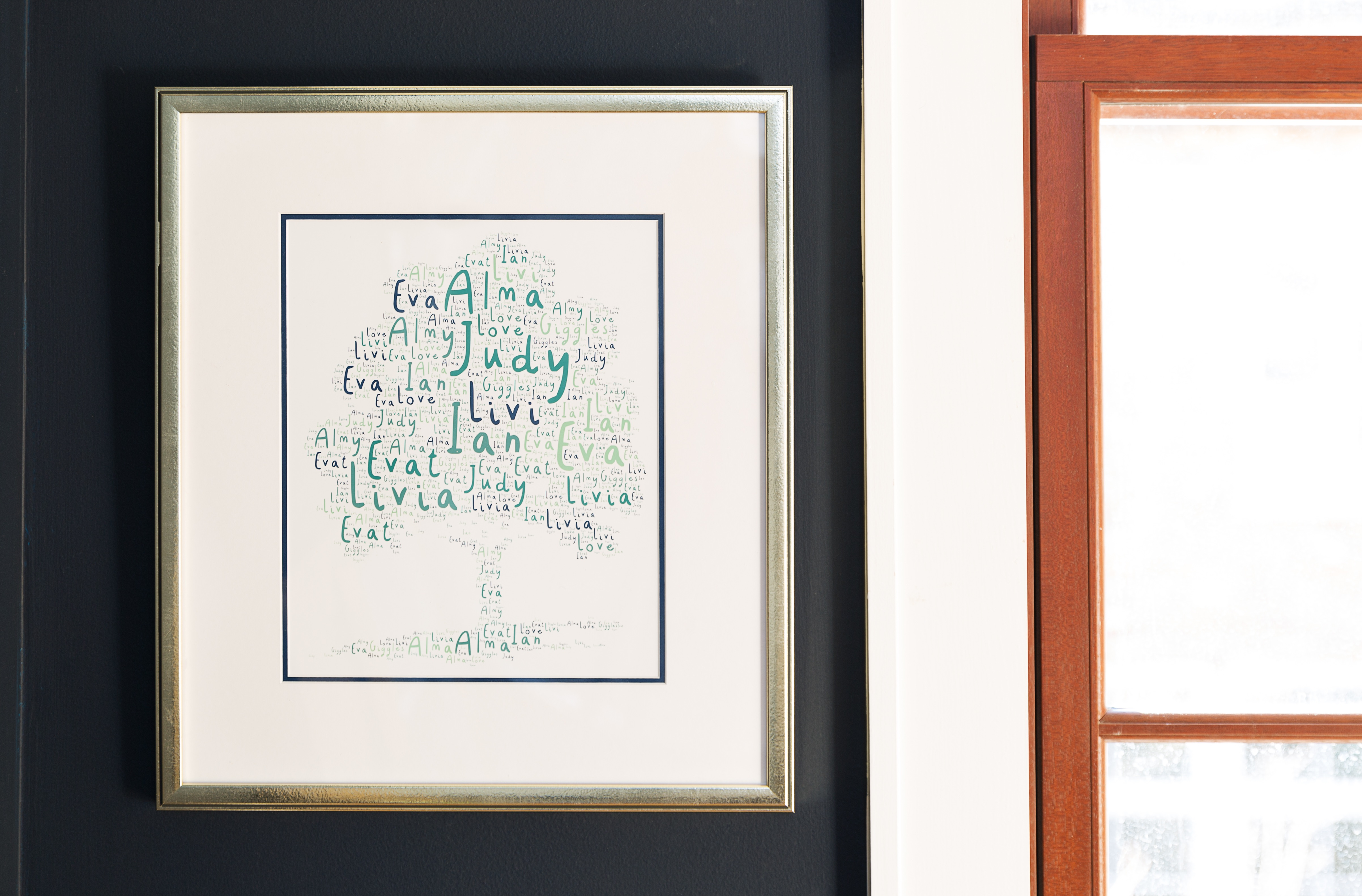 printable family tree in silver frame on navy wall next to a window