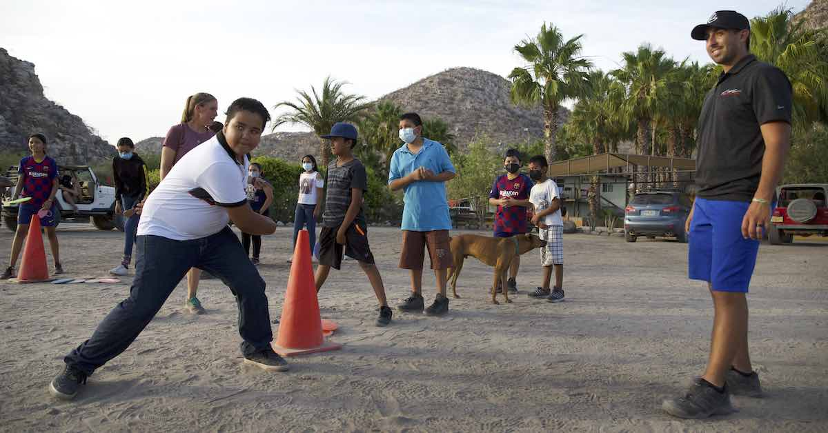 A child reaches back to throw a disc as a man in blue shorts and black shirt looks on. The scene is a mountainous desert with palm trees and others look on.