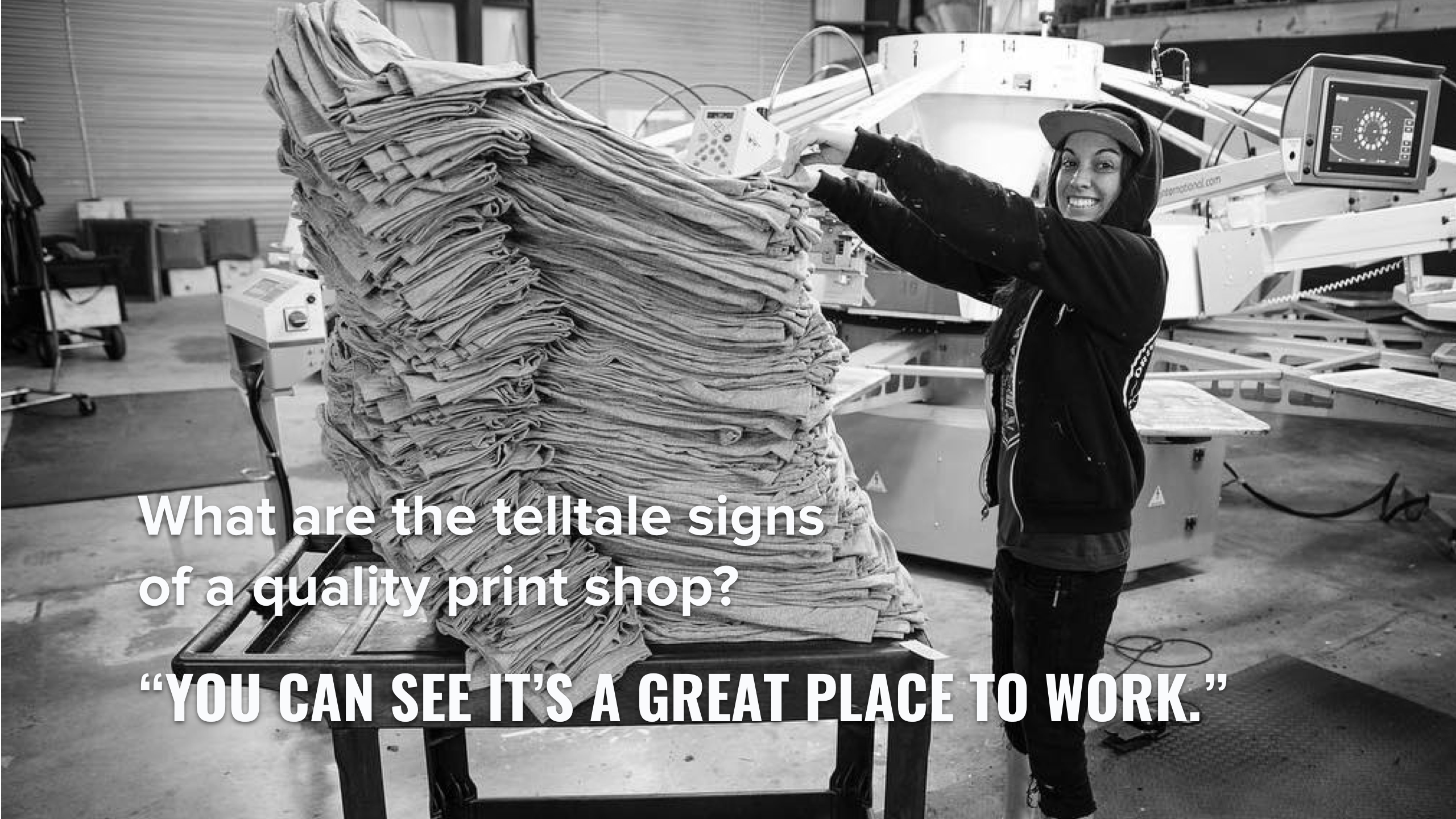 A screen printer with a large stack of shirts.