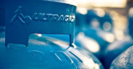 Foto da parte de cima de um botijão azul da Ultragaz, dando foco na alça do mesmo. O fundo está desfocado.